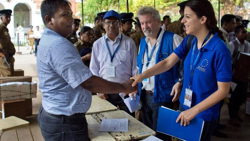 Despina Efstathiou, right, an election observer of European Union shakes hands with a Sri Lankan polling officer as her colleague Carl Olle, second right watches at a polling material distribution center in Colombo, Sri Lanka, Sunday, Aug. 16, 2015. The island nation holds parliamentary elections on August 17, 2015. (AP Photo/Gemunu Amarasinghe)