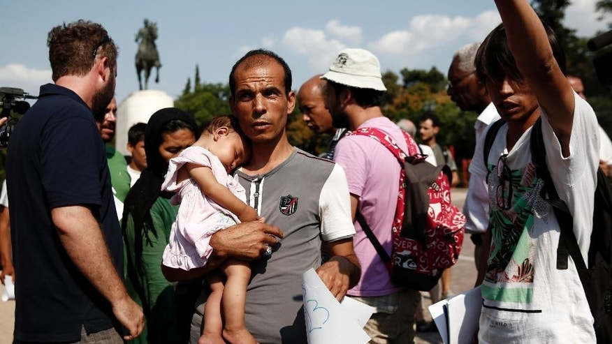 A migrant with his child makes his way to board a fire brigade bus to be transferred from a park to an organized camp which has been set up by the Greek state a few miles from the centre of Athens, Sunday, Aug. 16, 2015. Greek authorities say they have started resettling migrants living in tents in a park in the capital Athens, but many are wary of such a move and have moved to directions unknown thus far. (AP Photo/Yorgos Karahalis)