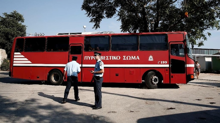 Policemen stand guard as a fire brigade bus carrying migrants enters an organized camp which has been set up by the Greek state a few miles from the centre of Athens, Sunday, Aug. 16, 2015. Greek authorities say they have started resettling migrants living in tents in a park in the capital Athens, but many are wary of such a move and have moved to directions unknown thus far. (AP Photo/Yorgos Karahalis)