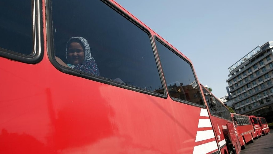 A migrant looks out from a fire brigade bus as she waits to be transferred from a park to an organized camp which has been set up by the Greek state a few miles from the centre of Athens, Sunday, Aug. 16, 2015. Greek authorities say they have started resettling migrants living in tents in a park in the capital Athens, but many are wary of such a move and have moved to directions unknown thus far. (AP Photo/Yorgos Karahalis)