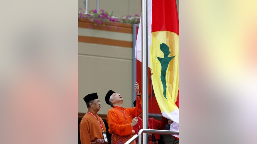 FILE - In this Oct. 21, 2010, file photo, Malaysian Prime Minister Najib Razak, right, raises the party's flag beside then deputy Muhyiddin Yassin during the Malaysia ruling party United Malays National Organization (UMNO) general assembly in Kuala Lumpur, Malaysia. Razak has a problem: he can's explain away a $700 million bank account to a skeptical public. Less than a month after leaked documents suggested that $700 million from entities linked to debt-ridden state investment fund 1MDB was funneled into Prime Minister Najib Razak's accounts, he has expelled critics in his government, sacked the attorney-general probing him, suspended two newspapers, blocked a UK-based website and stalled investigations over the scandal. (AP Photo/Lai Seng Sin, File)