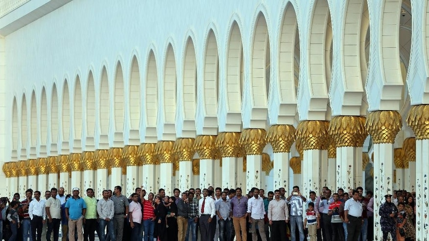 Indian expatriates wait in the courtyard of  the Sheikh Zayed Grand Mosque to see their Prime Minister, Narendra Modi, during the first day of a two-day visit to the UAE, in Abu Dhabi, United Arab Emirates, Sunday, Aug. 16, 2015. The UAE is home to over two million Indian expatriates and this is the first visit by an Indian premier in over three decades. (AP Photo/Kamran Jebreili)