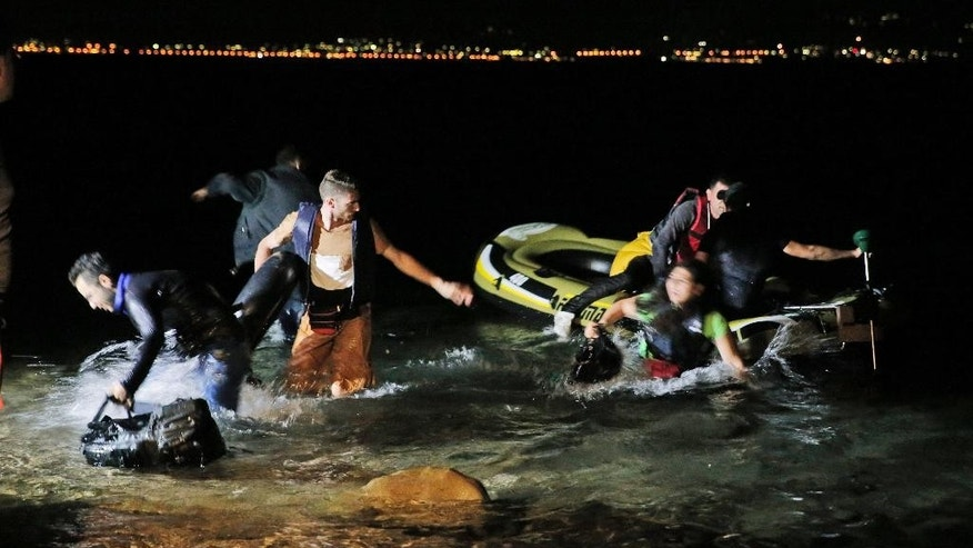 Migrants jump on the water after their overloaded dinghy started partially sinking, as they were trying to start their journey from the coastal town of Bodrum, Turkey, to the Greek island of Kos, seen in the background, early Sunday, Aug. 16, 2015. The migrants  abandoned their effort on this occasion due to a malfunctioned outboard motor. With the shores of Kos - a gateway to Europe - just a few kilometers (miles) away, hundreds of migrants are piling into tiny inflatable dinghies each night and attempting to make the crossing powered by tiny outboard motors and plastic paddles. (AP Photo/Lefteris Pitarakis)