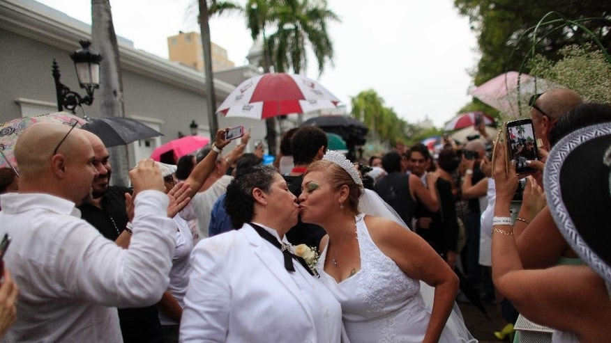 Alma Rosado,left, and Flor Maria Montijo, right, kiss after their wedding during a mass same-sex wedding in San Juan, Puerto Rico, Sunday, Aug. 16, 2015. Over 60 couples from around the region gathered in Puerto Rico's capital to exchange vows at a same-sex marriage ceremony. (AP Photo/Ricardo Arduengo)