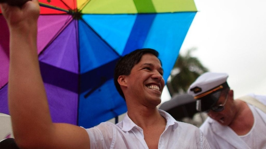 LGBT activist Pedro Julio Serrano, left, attends a mass same-sex wedding ceremony in San Juan, Puerto Rico, Sunday, Aug. 16, 2015. Over 60 couples from around the region gathered in Puerto Rico's capital to exchange vows at a same-sex marriage ceremony. (AP Photo/Ricardo Arduengo)
