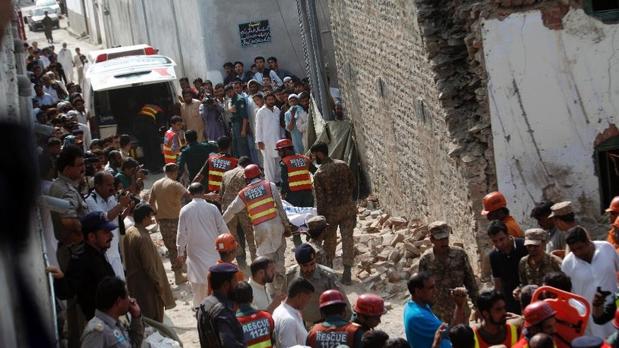 Pakistani rescue workers recover dead bodies from the rubble of the site of a suicide bombing, in Shadi Khan, some 80 kilometers (50 miles) northwest from the Pakistani capital, Sunday, Aug. 16, 2015.  A pair of suicide bombers detonated their explosives at the home of an anti-Taliban provincial minister, killing him and more than a dozen others in eastern Pakistan, officials said. (AP Photo/Anjum Naveed)