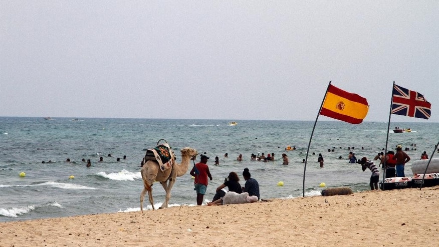 In this photo taken on Aug. 9, 2015, a Tunisian guide walks a camel offering rides along a crowded beach in Hammamet, Tunisia. The jet skis roar by the shore and the water is full of splashing children along the Tunisian Riviera, where despite the deadly attack that killed 38 tourists in June, the beaches are still full _ for now. Europeans have abandoned this North African country, leaving just local Tunisian beach-goers and visiting Algerians. But they will be gone by month's end, and then the real pain for the country's all-important tourism industry will begin. (AP Photo/Paul Schemm)