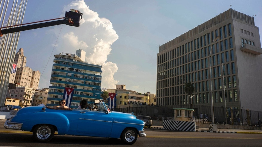 Tourists ride on a vintage American car in front of the U.S. embassy in Havana, Cuba, Thursday, Aug. 13, 2015. The US embassy in Cuba will hold a ceremony on Friday, Aug. 14, to raise the U.S. flag, to mark its reopening on Havanaâs historic waterfront. Ordinary Cubans will cheer, U.S. business executives will network and Secretary of State John Kerry will meet with Cubaâs foreign minister, the countryâs Roman Catholic archbishop and a hand-picked group of dissidents. (AP Photo/Ramon Espinosa)