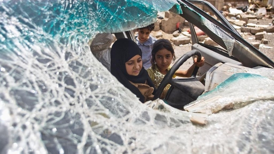 "FILE - In this May 18, 2015, file photo, Yemeni girls play with in a vehicle damaged by Saudi-led coalition airstrikes in Sanaa, Yemen. In a report released Tuesday, Aug. 18, Amnesty International says all sides fighting in Yemen have left a ""trail of civilian death and destruction"" in the conflict, killing scores of innocent people in what could amount to war crimes. The latest report accused both the Saudi-led coalition carrying out airstrikes in Yemen and attacks by forces supporting and opposing the rebels, known as Houthis. (AP Photo/Hani Mohammed, File)"