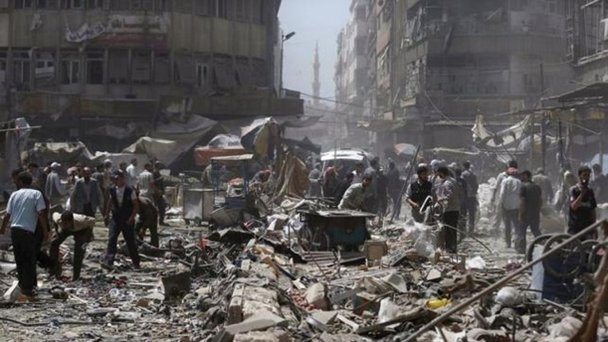 Aug. 16, 2015: People inspect a site hit by what activists said were air strikes by forces loyal to Syria's President Bashar al-Assad on a marketplace in the Douma neighborhood of Damascus, Syria. (REUTERS/BASSAM KHABIEH)