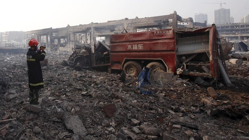 In this photo taken Saturday Aug. 15, 2015, a firefighter inspects a destroyed fire truck at the site of an explosion in northeastern China's Tianjin municipality. The rapid chain of explosions that destroyed a warehouse district in the Chinese port of Tianjin could become one of the world's deadliest disasters for fire crews. Now questions are being raised about whether the crews were properly trained and equipped to deal with the emergency at a warehouse that stored a volatile mix of chemicals, including compounds that become combustible on contact with water. (Chinatopix Via AP) CHINA OUT