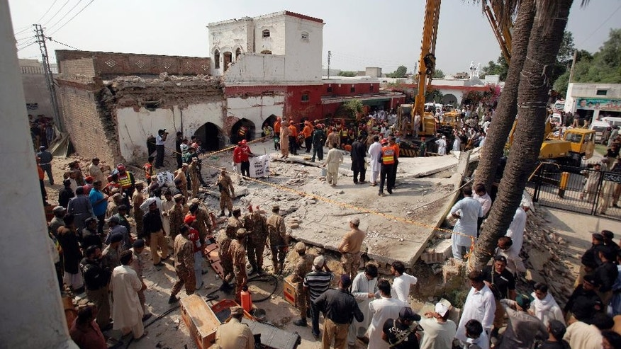 Pakistani Army troops and rescue workers gather at the site of suicide bombing in Shadi Khan, some 80 kilometers (50 miles) northwest from Pakistani capital, Sunday, Aug. 16, 2015. A pair of suicide bombers detonated their explosives at the home of an anti-Taliban provincial minister, killing him and more than a dozen others in eastern Pakistan, officials said. (AP Photo/Anjum Naveed)
