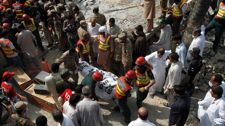 Pakistani rescue workers carry a dead body after recovering from the rubble at the site of suicide bombing in Shadi Khan, some 80 kilometers (50 miles) northwest from Pakistani capital, Sunday, Aug. 16, 2015.  A pair of suicide bombers detonated their explosives at the home of an anti-Taliban provincial minister, killing him and more than a dozen others in eastern Pakistan, officials said. (AP Photo/Anjum Naveed)