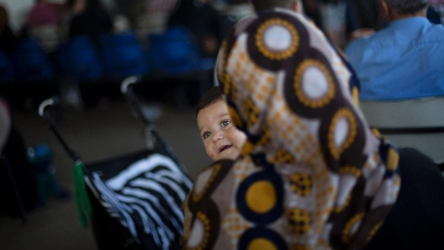 A Palestinian woman carries her child as she waits to cross the border into Egypt, at the Rafah crossing in the southern Gaza Strip, Monday, Aug 17, 2015. Egypt opened its border with the Gaza Strip Monday for the first time in two months. The Rafah border crossing opened Monday for four days, allowing Palestinians to travel in both directions.(AP Photo/ Khalil Hamra)