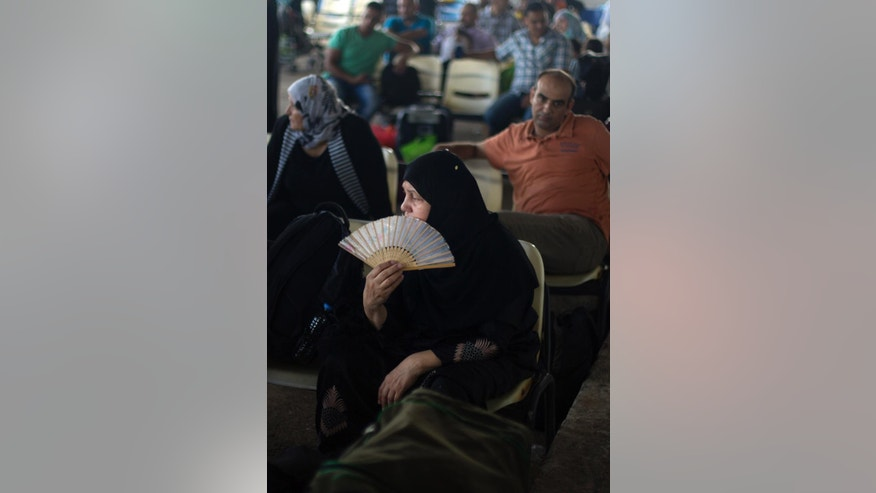 A Palestinian woman uses a fan for the heat as she waits to cross the border into Egypt, at the Rafah crossing in the southern Gaza Strip, Monday, Aug 17, 2015. Egypt opened its border with the Gaza Strip Monday for the first time in two months. The Rafah border crossing opened Monday for four days, allowing Palestinians to travel in both directions. (AP Photo/ Khalil Hamra)