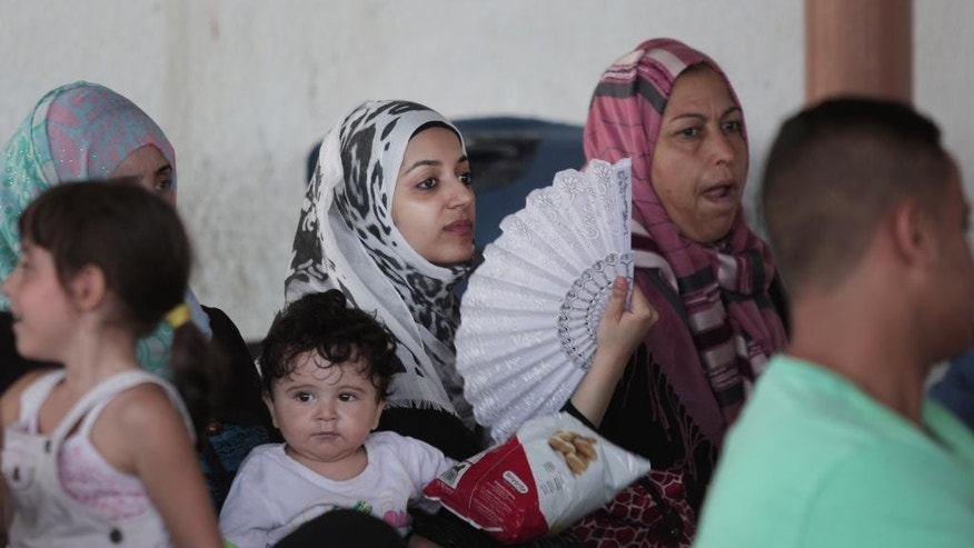 A Palestinian woman uses a fan for the heat as she waits to cross the border into Egypt, at the Rafah crossing in the southern Gaza Strip, Monday, Aug 17, 2015. (AP Photo/Khalil Hamra)