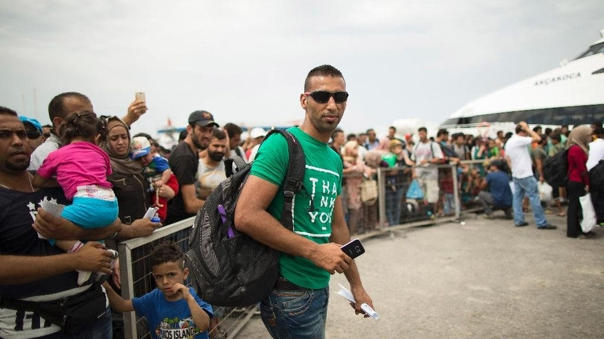 In this photo taken on Saturday, Aug. 15, 2015, Syrian former rebel commander Laith Al Saleh, 30, waits with other refugees to board an Athens-bound ferry on the Greek island of Kos. Al Saleh had a home, a wife and a normal life, before the start of the fighting that has claimed more than 250,000 lives and displaced up to a third of Syria's population. Now, he's one of the tens of thousands of Syrian men, women and children who risk drowning to be smuggled into Greece by sea on frail, crammed dinghies, paying up to thousands of dollars for the service. At least 135,000 people - mostly Syrians  have crossed over from Turkey this year, more than the total for all of 2014 and 2013 together. (AP Photo/Alexander Zemlianichenko)