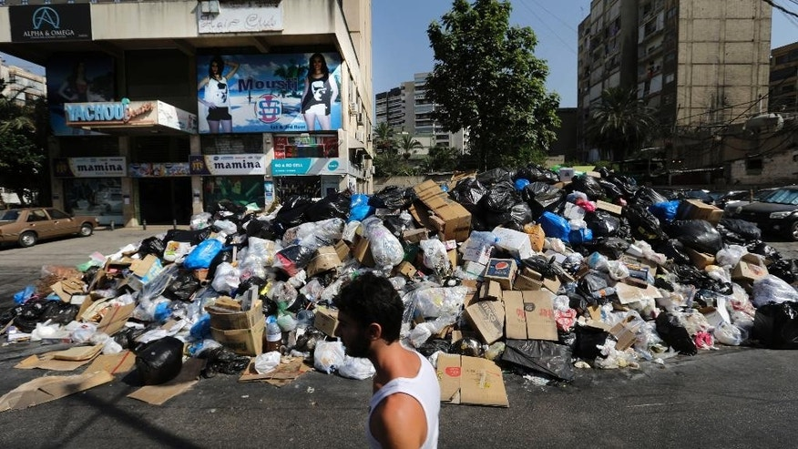 "A Lebanese man passes a pile of garbage blocking a street in east Beirut, Lebanon, Monday, Aug. 17, 2015. Health Minister Wael Abu Faour said Monday that the country is on the brink of a ""major health disaster"" unless an immediate solution is found for the country's trash. Garbage has been collecting on streets in Lebanon for the past month amid government paralysis and inability to agree on a solution after Beirut's main landfill was closed down. (AP Photo/Hassan Ammar)"