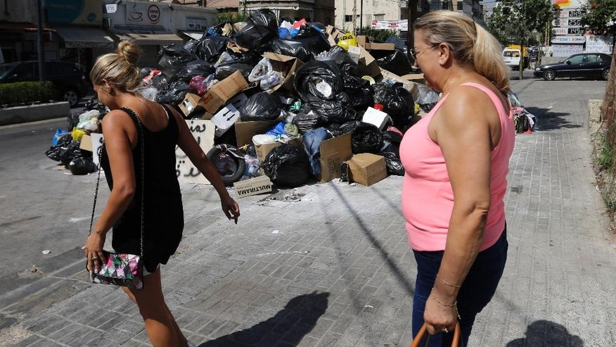 "Lebanese women pass a pile of garbage blocking a street in east Beirut, Lebanon, Monday, Aug. 17, 2015. Health Minister Wael Abu Faour said Monday that the country is on the brink of a ""major health disaster"" unless an immediate solution is found for the country's trash. Garbage has been collecting on streets in Lebanon for the past month amid government paralysis and inability to agree on a solution after Beirut's main landfill was closed down. (AP Photo/Hassan Ammar)"