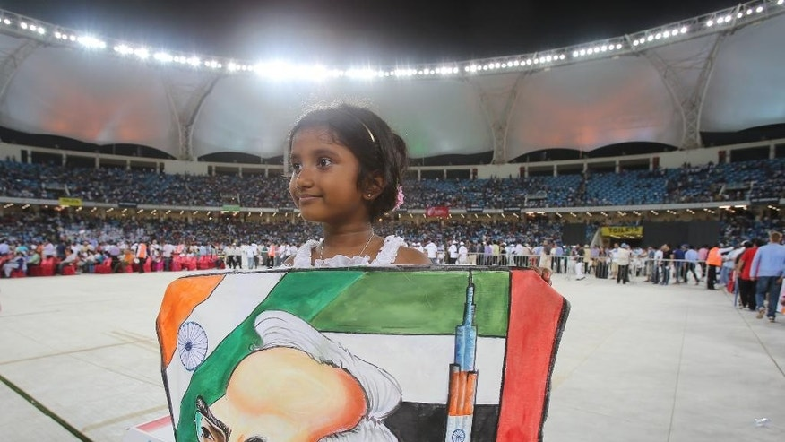 An Indian girl holds a poster depicting her Prime Minister, Narendra Modi, during his speech at a cricket stadium, Monday, Aug. 17, 2015, in Dubai, United Arab Emirates. The UAE is home to over two million Indian expatriates and this is the first visit by an Indian premier in over three decades. (AP Photo/Kamran Jebreili)
