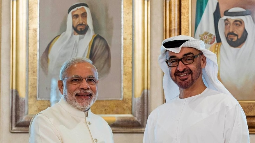 In this photo made available by Crown Prince Court, Abu Dhabi, Sheikh Mohamed bin Zayed Al Nahyan, Crown Prince of Abu Dhabi and Deputy Supreme Commander of the UAE Armed Forces, right, shakes hands with Narendra Modi, Prime Minister of India at the Emirates Palace hotel in Abu Dhabi, United Arab Emirates, Monday, Aug. 17, 2015. (Ryan Carter/Crown Prince Court, Abu Dhabi, via AP)