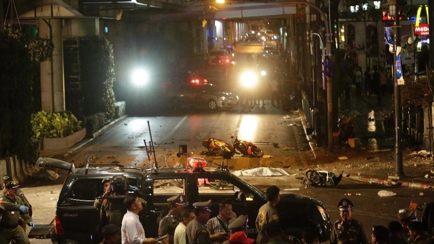 Officials close off an intersection after an explosion in Bangkok, Monday, Aug. 17, 2015. A large explosion rocked a central Bangkok intersection during the evening rush hour, killing a number of people and injuring others, police said. (AP Photo/Sackchai Lalit)