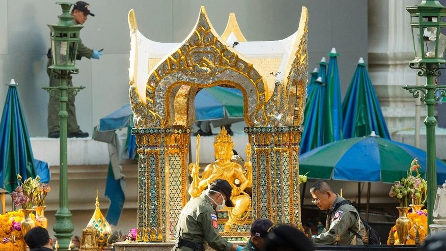 Police investigators work near the statue of Phra Phrom, which is the Thai interpretation of the Hindu god Brahma, at the Erawan Shrine the morning after an explosion in Bangkok, Thailand, Tuesday, Aug. 18, 2015. A bomb exploded Monday within a central Bangkok shrine that is among the city's most popular tourist spots, killing a number of people and injuring others, police said. (AP Photo/Mark Baker)