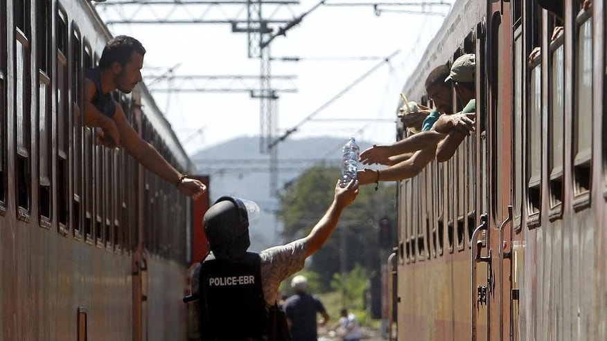 Police officer passes a bottle of water to migrants on the train towards Serbia, at the railway station in the southern Macedonian town of Gevgelija, on Monday, Aug. 17, 2015. Over 1,000 migrants from Middle East, Asia and Africa, enter Macedonia daily from Greece, heading north through the Balkans on their way to the more prosperous European Union countries. The migrants' urgency to reach Europe has become more pronounced as they race to reach Hungary before the Hungarian government finishes building a razor-wire fence. (AP Photo/Boris Grdanoski)