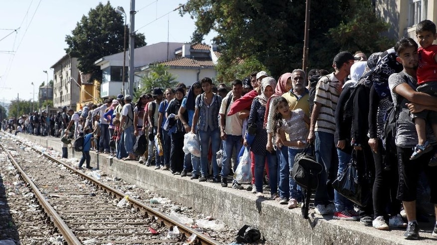 Migrants line up to board a train that would take them towards Serbia, at the railway station in the southern Macedonian town of Gevgelija, on Monday, Aug. 17, 2015. Over 1,000 migrants from Middle East, Asia and Africa, enter Macedonia daily from Greece, heading north through the Balkans on their way to the more prosperous European Union countries.  (AP Photo/Boris Grdanoski)