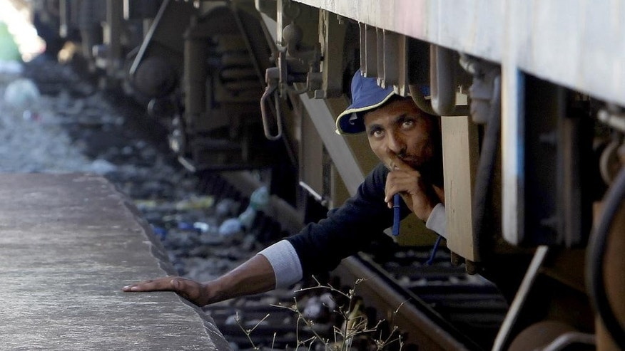 A migrant, hiding under a train, tries to sneak on a train towards Serbia, at the railway station in the southern Macedonian town of Gevgelija, on Monday, Aug. 17, 2015. Over 1,000 migrants from Middle East, Asia and Africa, enter Macedonia daily from Greece, heading north through the Balkans on their way to the more prosperous European Union countries. The migrants' urgency to reach Europe has become more pronounced as they race to reach Hungary before the Hungarian government finishes building a razor-wire fence. (AP Photo/Boris Grdanoski)