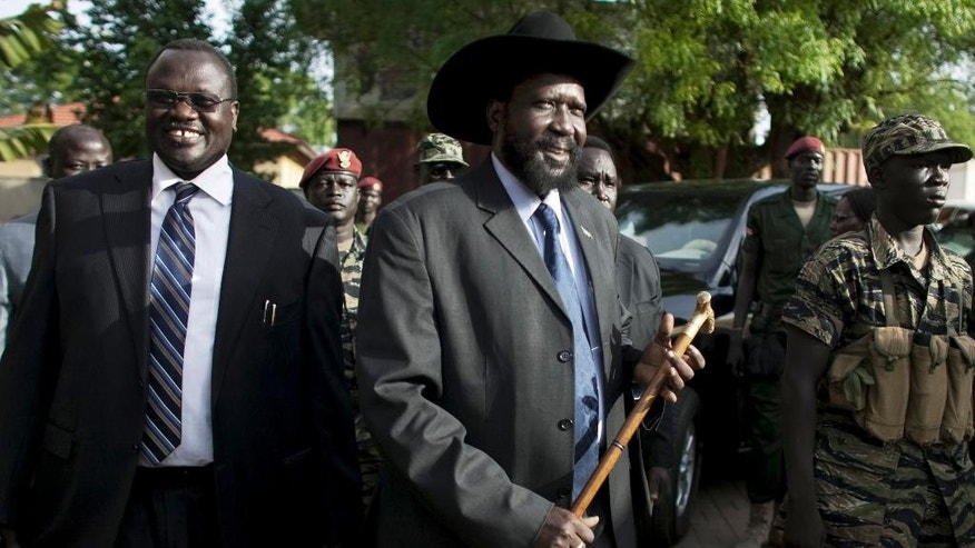 FILE - In this Monday, April 26, 2010 file photo, then Vice President Riek Machar, left, and President of South Sudan Salva Kiir, centre, arrive for a press conference in Juba, South Sudan. Mediators say President Salva Kiir of South Sudan and rebel leader Riek Machar are expected to sign a peace agreement in Addis Ababa, Ethiopia on Monday, Aug. 17, 2015, with the U.S. urging the warring factions to reach a peace agreement by that date or face sanctions. (AP Photo/Pete Muller, File)