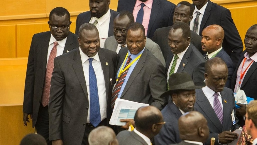 South Sudan's rebel leader Riek Machar, second left, looks across after shaking hands with South Sudan's President Salva Kiir, center-right wearing a black hat, after lengthy peace negotiations in Addis Ababa, Ethiopia Monday, Aug. 17, 2015. South Sudan's President Salva Kiir refused to sign a peace agreement Monday with rebel forces, saying he needs 15 days before he will sign, although rebel leader Riek Machar had signed the accord before Kiir refused. (AP Photo/Mulugeta Ayene)