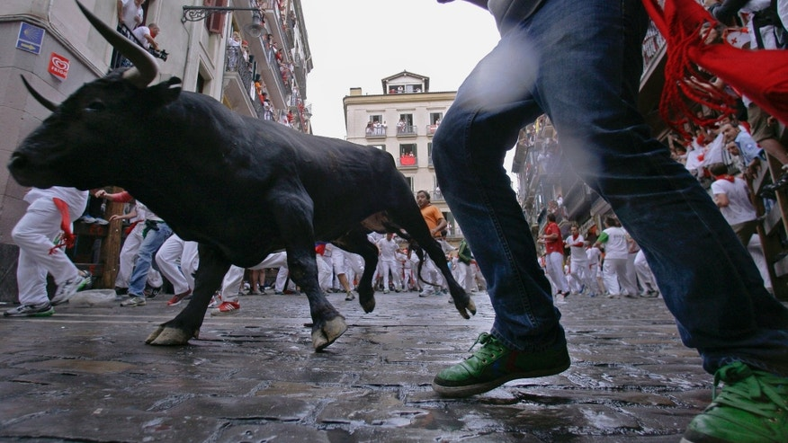 CORRECTS THE STAGE OF THE EVENT TO SECOND RUNNING - Revelers run on the  Estafeta corner as a fighting bull from Miura ranch go on the way during the second running of the bulls at the San Fermin fiestas, in Pamplona northern Spain, Sunday, July 8, 2012. (AP Photo/Alvaro Barrientos)