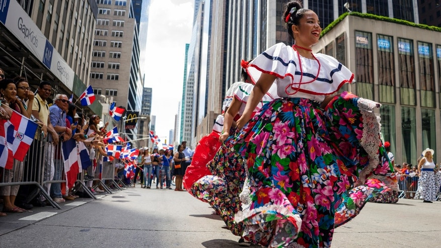 Participants dance along Sixth Ave. during the Dominican Day Parade Sunday, Aug. 9, 2015, in New York. The parade, held annually each August along Sixth Avenue, began in 1982. (AP Photo/Craig Ruttle)