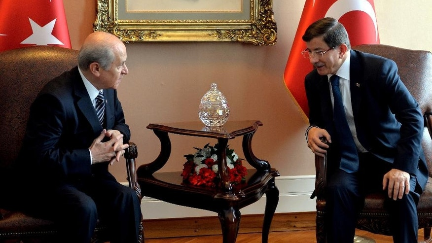 Turkish Prime Minister and leader of Justice and Development Party Ahmet Davutoglu, right, speaks with Turkey's Nationalist Movement Party leader Devlet Bahceli before a meeting to discuss forming a coalition government, in Ankara, Turkey, Monday, Aug.17, 2015. Davutoglu's efforts to forge a coalition alliance with the country's pro-secular party have failed last week, edging the country closer toward new elections. His Islamic-rooting ruling party lost its majority in elections in June, forcing it to seek a coalition alliance to remain in power.(AP Photo)