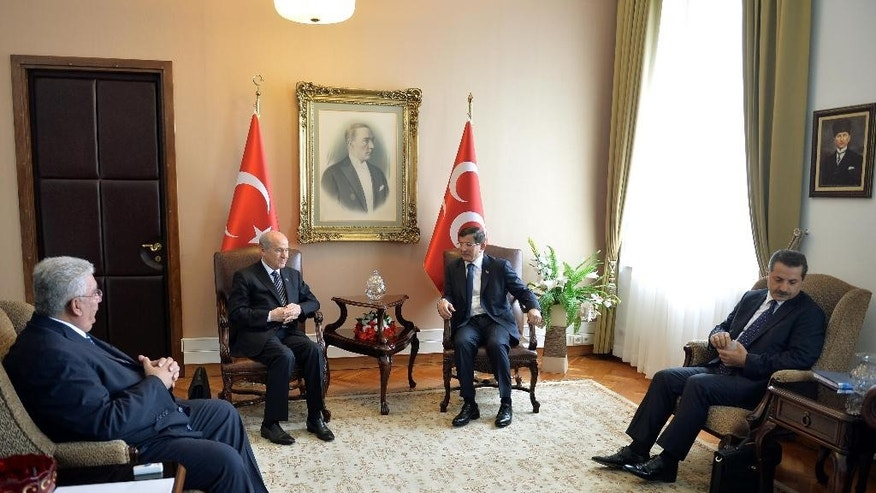 Turkish Prime Minister and leader of Justice and Development Party, AKP, Ahmet Davutoglu, center right, speaks with Turkey's Nationalist Movement Party, MHP, leader Devlet Bahceli, second left, before a meeting to discuss forming a coalition government, in Ankara, Turkey, Monday, Aug.17, 2015. Davutoglu's efforts to forge a coalition alliance with the country's pro-secular party have failed last week, edging the country closer toward new elections. His Islamic-rooting ruling party lost its majority in elections in June, forcing it to seek a coalition alliance to remain in power. At left is MHP's Semih Yalcin, and at right AKP Faruk Celik. (AP Photo)