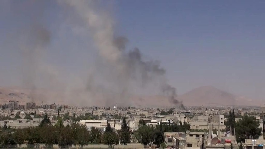 "This image made from video posted online by the Shaam News Network, a loosely organized group opposed to Bashar Assad, on Sunday, Aug. 16, 2015, which has been verified and is consistent with other AP reporting, shows smoke riding from Syrian government airstrikes in Douma, a suburb of Damascus, Syria. The United Nations humanitarian chief said on Monday he is ""horrified"" by the attacks on civilians taking place in Syria, singling out in particular government airstrikes the previous day that killed nearly 100 people in a Damascus suburb. (Shaam News Network via AP video)"