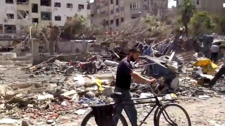 "This image made from video posted online by the Shaam News Network, a loosely organized group opposed to Bashar Assad, on Sunday, Aug. 16, 2015, which has been verified and is consistent with other AP reporting, shows the aftermath of Syrian government airstrikes in Douma, a suburb of Damascus, Syria. The United Nations humanitarian chief said on Monday he is ""horrified"" by the attacks on civilians taking place in Syria, singling out in particular government airstrikes the previous day that killed nearly 100 people in a Damascus suburb.(Shaam News Network via AP video)"