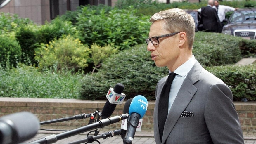 Finnish Finance Minister Alexander Stubb speaks with the media as he arrives for a meeting of eurozone finance ministers at the EU Council building in Brussels on Friday, Aug. 14, 2015. (AP Photo/Francois Walschaerts)