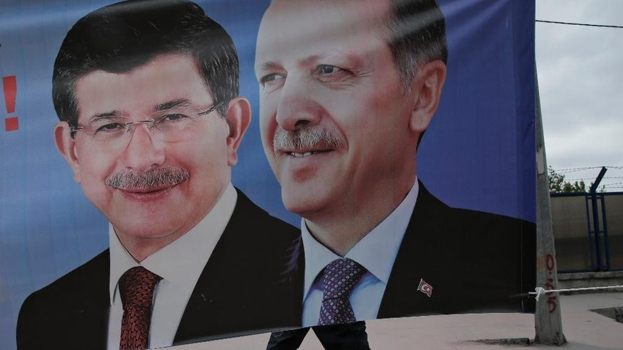 FILE - In this Thursday, May 28, 2015 file photo, a man walks past a poster with pictures of Turkish Prime Minister and leader of the AKP party Ahmet Davutoglu, left, and Turkey's President Recep Tayyip Erdogan and party's former leader, right, in Istanbul. After his party suffered major losses in June elections, Erdogan seems to be back in control and edging Turkey towards repeat elections, and gambling that a new ballot could revive his fortunes. (AP Photo/Lefteris Pitarakis, FILE)
