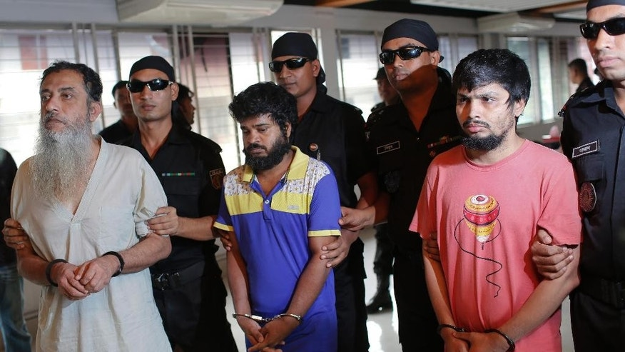 Bangladesh Rapid Action Battalion personnel in black, present before media, suspected members of a banned Islamic militant outfit Ansarullah Bangla Team, Touhidur Rahman, second left, Sadek Ali, center and Aminul Mollick, second right in Dhaka, Bangladesh, Tuesday, Aug. 18, 2015. An anti-crime agency in Bangladesh said Tuesday they have arrested three men, including Touhidur Rahman a British citizen, for their involvement in the murders of two secular bloggers.( AP Photo/ A.M. Ahad)
