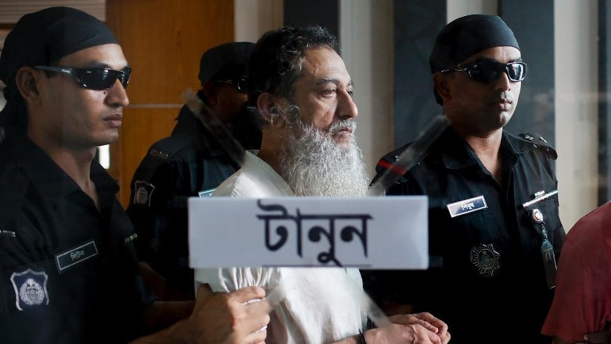 "Bangladesh Rapid Action Battalion personnel in black, present before media, suspected member of a banned Islamic militant outfit Ansarullah Bangla Team, Touhidur Rahman, along with two others in Dhaka, Bangladesh, Tuesday, Aug. 18, 2015. An anti-crime agency in Bangladesh said Tuesday they have arrested three men, including Touhidur Rahman a British citizen, for their involvement in the murders of two secular bloggers. Sign on the glass in Bangla reads, ""Pull''. ( AP Photo/ A.M. Ahad)"