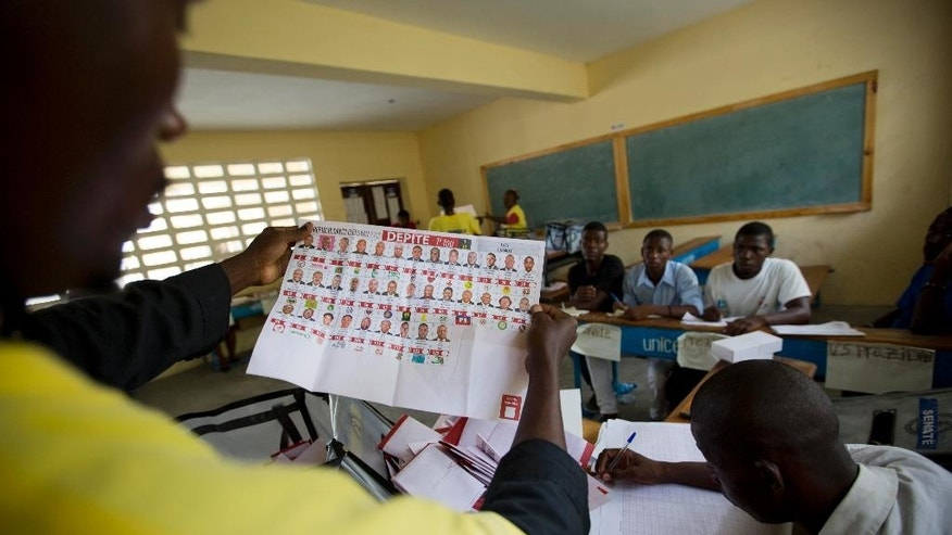 FILE - In this Aug. 9, 2015 file photo, election officials count votes during parliamentary elections in Port-au-Prince, Haiti. Electoral officials disqualified nine candidates Tuesday, Aug. 18, 2015, for engaging in violence or inciting chaos during recent Haiti's parliamentary elections. (AP Photo/Dieu Nalio Chery, File)