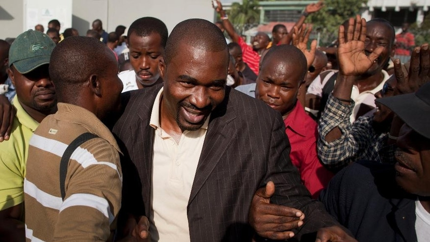 FILE - In this Oct. 28, 2011 file photo, Haitian lawmaker Arnel Belizaire is greeted by supporters upon his arrival to Parliament in Port-au-Prince, Haiti. Electoral officials in Haiti disqualified nine candidates including Belizaire, Tuesday, Aug. 18, 2015, for engaging in violence or inciting chaos during recent parliamentary elections. The former opposition member of the Chamber of Deputies is accused of firing a weapon in the air outside a polling station in the capital. (AP Photo/Ramon Espinosa, File)