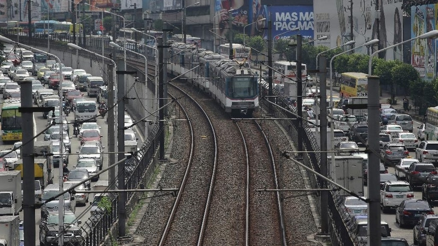 In this Tuesday, Aug. 11, 2015 photo, a train of the Manila Metro Rail Transit System travels in between Epifanio de los Santos Avenue (EDSA) during rush hour traffic in the financial district of Makati, south of Manila, Philippines. Manila and other cities are choked with construction sites for office and apartment towers. But spending on roads, railways and other unglamorous but essential infrastructure collapsed after the 1997 financial crisis and has yet to recover. (AP Photo/Aaron Favila)