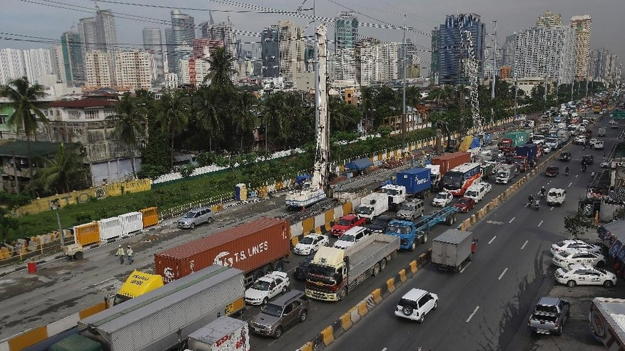 In this Wednesday, Aug. 12, 2015 photo, traffic snarls as several lanes are occupied by an ongoing government road project in the financial district of Makati, south of Manila, Philippines. Manila and other cities are choked with construction sites for office and apartment towers. But spending on roads, railways and other unglamorous but essential infrastructure collapsed after the 1997 financial crisis and has yet to recover. (AP Photo/Aaron Favila)