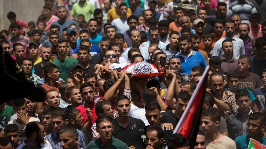 Palestinians carry the body of Mohammed Amsha, 25, during his funeral in the village of Kafr Rai near the West Bank city of Jenin, Tuesday, Aug. 18, 2015. Israeli authorities say Amsha was shot and killed Monday after he stabbed a guard at a West Bank checkpoint, slightly wounding him. (AP Photo/Majdi Mohammed)