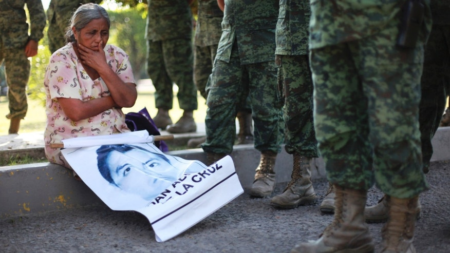 FILE - In this Dec. 18, 2014 file photo, the mother of missing college student Adan Abarajan de la Cruz sits at the foot of soldiers outside a military base during a protest by the families of 43 missing students over the army's alleged responsibility or lack of response to the students' disappearance in Iguala, Mexico. A group of independent experts said Monday, Aug. 17 2015, that Mexican authorities withheld information from family members of 43 college students who disappeared after a confrontation with police, not notifying them that some of the young menâs clothing was discovered shortly after they went missing. (AP Photo/Felix Marquez, File)