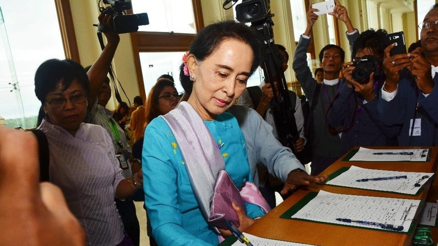 Myanmar opposition leader Aung San Suu Kyi signs on registration book upon arrival to attend a regular session at Parliament in Naypyitaw, Myanmar Tuesday, Aug. 18, 2015. Parliament has reopened for its final session before Myanmar's nationwide election, with a spotlight on the influential speaker following his violent ouster as head of the military-backed ruling party. (AP Photo/Khin Maung Win)