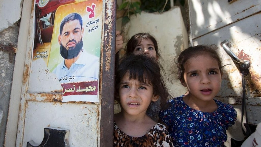 "FILE - In this Sunday, Aug. 9, 2015 file photo, Palestinian girls, from left, Ghofran, Lane, and Mary stand next to a poster showing their uncle Mohammed Allan at the family house in the village of Einabus, near the West Bank city of Nablus. Allan spent his college years as an activist, fighting for Palestinian rights as a member of the student wing of the Palestinian Islamic Jihad militant group. Now, verging on death and shackled to a hospital bed, the man accused by Israel of affiliation with terrorists has put a spotlight on Israel's controversial detention and force-feeding policies. Arabic reads, ""No to administrative detention."" (AP Photo/Majdi Mohammed, File)"